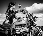 MOSCOW, RUSSIA-JULY 7, 2013: Biker girl on Legendary bike Harley Sportster. Processed in B&W. Harley-Davidson sustains a large brand community which keeps active through clubs, events, and a museum.