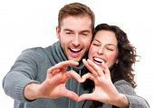 Valentine Couple. Portrait of Smiling Beauty Girl and her Handsome Boyfriend making shape of Heart by their Hands. Happy Joyful Family. Love Concept. Heart Sign. Laughing Happy Lovers. Valentines Day poster