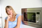 Portrait of woman by microwave oven