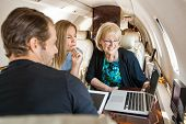 Business people working together on laptop in private jet