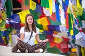 Teengirl sitting on Buddhist stupa, prayer flags flying in background.