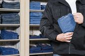 stock photo of shoplifting  - jeans being stolen by a shoplifter in a shop - JPG