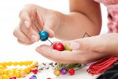 picture of thong  - A closeup of hand stringing colorful wooden beads on a thong - JPG