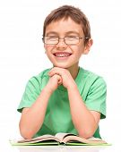 Cute little boy is reading a book while wearing glasses supporting his head with hands, isolated ove