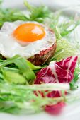 Beef tartar with fried egg and lettuce, close-up