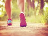 an athletic pair of legs running or jogging on a path during sunrise or sunset - healthy lifestyle concept done with a soft glowing filter