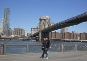 Young couple taking selfie in the front of Brooklyn Bridge