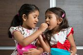 Indian girls sharing food, murukku with each other. Asian sibling or children living lifestyle at ho