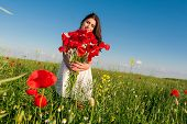Beautiful young woman over Sky and Sunset in the field holding a poppies bouquet, smiling.