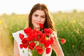 Beautiful Girl over Sky and Sunset in the field holding a poppies bouquet and smiling