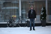 Winter. The man standing near the bicycle.