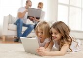 family, children, technology and home concept - smiling sister with tablet pc computer and parents o