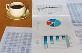 forecasting and analyzing incomes charts and graphs report with coffee cup, reverse angle