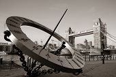 Tower Bridge and sundial over Thames River in London.