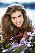 stock photo of girl next door  - Young beautiful girl next door with purple flowers in summer - JPG