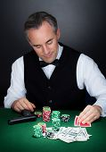 Portrait Of A Croupier Looking At Cards