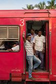 HIKKADUWA, SRI LANKA - FEBRUARY 22, 2014: Local people standing in the train doorway. Taking the tra