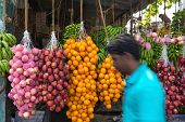 HIKKADUWA, SRI LANKA - FEBRUARY 22, 2014: Local man passing by street fruit stand. Most famous are stands  at Sunday market.