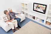 Senior Couple Changing Channel Of Television