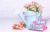 Beautiful bouquet of freesias in watering can in room