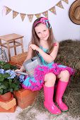 Beautiful small girl in petty skirt holding watering can on country style background