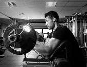 foto of preacher  - biceps preacher bench arm curl workout man at fitness gym - JPG