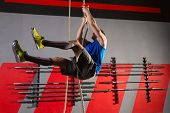 stock photo of climb up  - Rope Climb exercise man workout at gym climbing - JPG