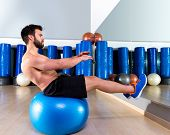 Fitball abdominal balance crunch Swiss ball man at fitness gym