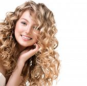 Beauty girl with blonde curly hair. Healthy and long Blond Wavy hair. Beautiful smiling young woman