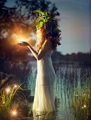 Fantasy girl taking magic light in her hands. Mysterious Night scene. Witch standing in the river an
