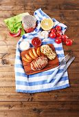 Grilled steak, grilled vegetables and fried potato pieces on wooden board on table background