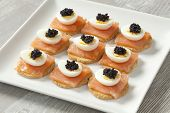 Snack with salmon,quail eggs and lumpfish roe on toast