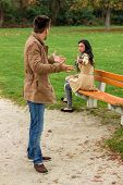 a young couple sitting on a park bench and fight