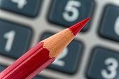 a red pen is on a calculator. save on costs, expenditures and budget for bad economy