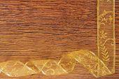 golden ribbon frame on wooden surface
