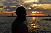 image of humility  - woman traveler standing at sunset on the sea beach - JPG