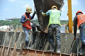 Group of construction workers casting concrete wall