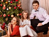 Happy family with children  dressing Christmas tree.