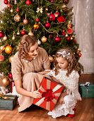 Happy child with mother receiving gifts under Christmas tree.