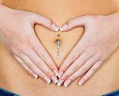 a woman has abdominal pain or stomach pain. hands in heart shape around navel piercing.
