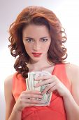 a beautiful woman in a pink dress with dollar banknotes in the hands