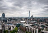 LONDON - 09 JUNE 2013: Aerial London cityscape looking over rooftops towards the Shard on a stormy cloudy day on 09 June 2013