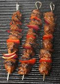 Lamb kebabs cooking on griddle plate