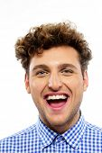 Portrait of a young laughing man on white background