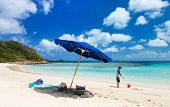 Kids playing on picture perfect beach with blue umbrella, white sand, turquoise ocean water and blue sky at tropical island in Caribbean