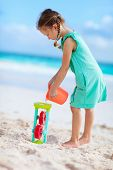 Adorable little girl playing at beach during summer vacation