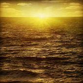 Seascape at sunset in grunge and retro style.