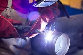 foto of pipe-welding  - welder in factory with protective equipment welding metal pipes - JPG