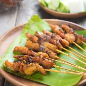 Yummy chicken sate or satay, skewered and grilled meat, served with peanut sauce. Fresh cooked with steamed and smoke. Hot and spicy Asian dish.