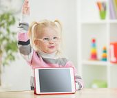 happy child in glasses with hand up and tablet pc screen